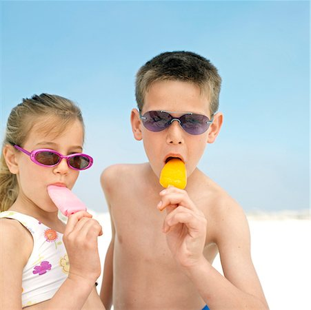 Boy (12-13 years) and girl (8-9 years) eating ice creams on beach portrait Stock Photo - Premium Royalty-Free, Code: 618-01738828