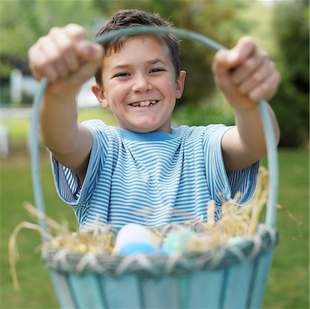 Boy (8-9) holding basket of eggs, outdoors, portrait Stock Photo - Premium Royalty-Free, Code: 618-01738904