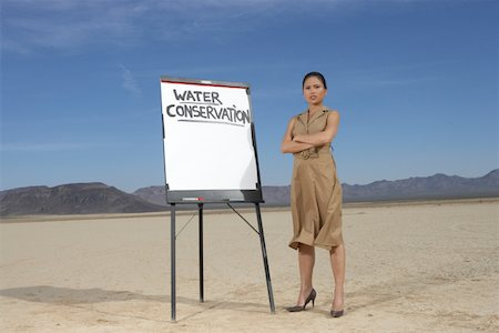 desert people dress photos - Businesswoman beside sign stressing water conservation Stock Photo - Premium Royalty-Free, Code: 618-01836850