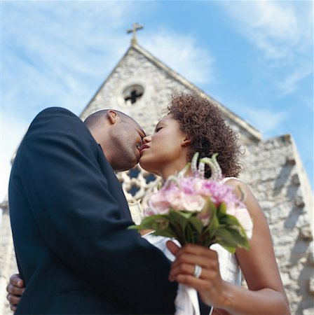 Newlywed couple kissing outside church, low angle view Stock Photo - Premium Royalty-Free, Code: 618-01885811