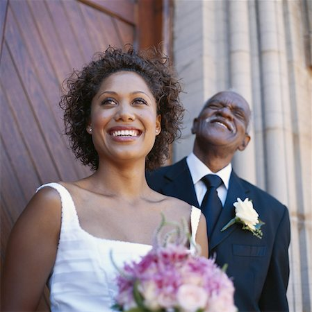 Bride standing with father outside church, smiling, low angle view Stock Photo - Premium Royalty-Free, Code: 618-01885863