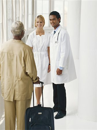 Female nurse and doctor talking with patient holding suitcase Stock Photo - Premium Royalty-Free, Code: 618-01886234