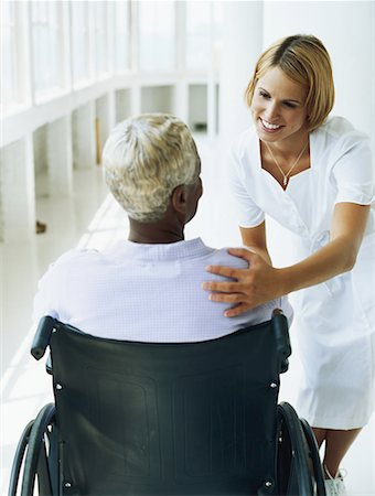Female nurse talking with patient sitting on wheelchair Stock Photo - Premium Royalty-Free, Code: 618-01886235