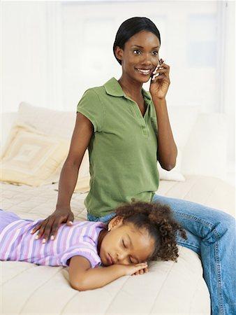 Woman sitting by sleeping girl (4 5), using mobile phone Stock Photo - Premium Royalty-Free, Code: 618-01886405