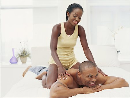 Young couple in bedroom, woman massaging man, smiling Stock Photo - Premium Royalty-Free, Code: 618-01886853