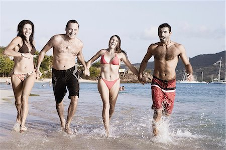 Two mid adult couples holding hands and running on the beach Stock Photo - Premium Royalty-Free, Code: 618-03570999