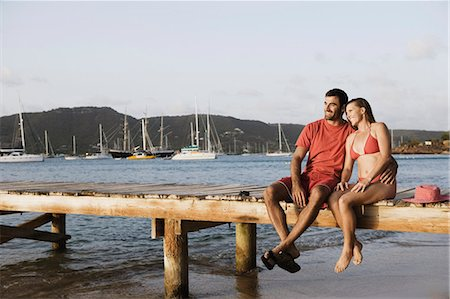 Mid adult man with his arm around a mid adult woman and sitting on a jetty Stock Photo - Premium Royalty-Free, Code: 618-03571003