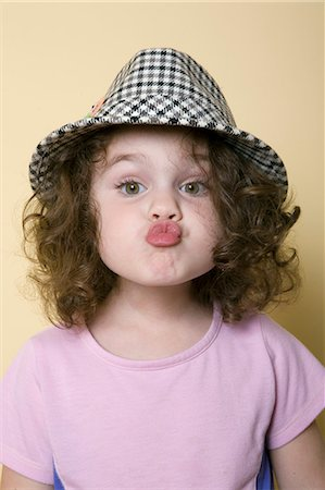 pucker - Young girl wearing hat making a kissing face. Stock Photo - Premium Royalty-Free, Code: 618-03571374