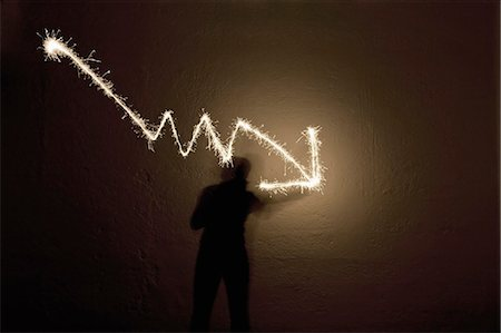 silhouette of firework - Shadow of person making arrow sign with sparkler Stock Photo - Premium Royalty-Free, Code: 618-03571544