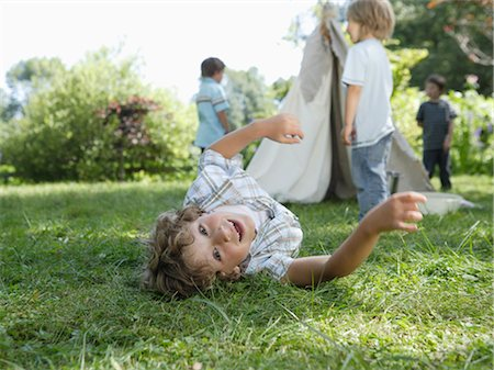 Young boy laying in grass with boys at tipi in background Stock Photo - Premium Royalty-Free, Code: 618-03571716