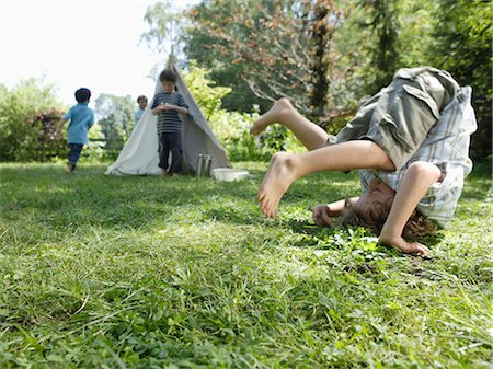 Young boy doing somersault in grass, boys in background Stock Photo - Premium Royalty-Free, Code: 618-03571797