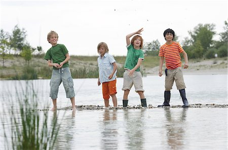 Portrait of four boys standing in pond Stock Photo - Premium Royalty-Free, Code: 618-03571807