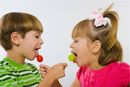picture of a red lollipop - Boy and girl enjoying green and red lollipops Stock Photo - Premium Royalty-Free, Code: 618-03610032