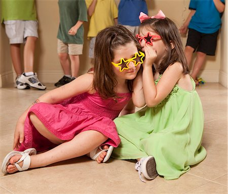 girls whispering with kids in background Stock Photo - Premium Royalty-Free, Code: 618-03610063