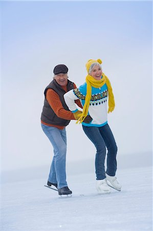 Senior man guiding mature woman on ice, smiling Stock Photo - Premium Royalty-Free, Code: 618-03610773
