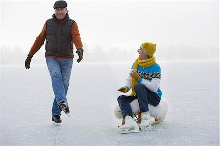 Senior man ice skating by mature woman sitting on ice sled Stock Photo - Premium Royalty-Free, Code: 618-03610789
