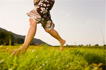 Woman running barefoot through grass, low section Stock Photo - Premium Royalty-Free, Code: 618-03610853