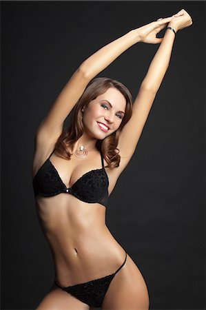 Young woman standing in black underwear, smiling Stock Photo - Premium Royalty-Free, Code: 618-03611431
