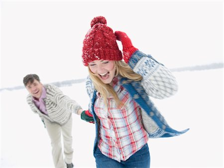 A young couple running through the snow holding hands Stock Photo - Premium Royalty-Free, Code: 618-03612585
