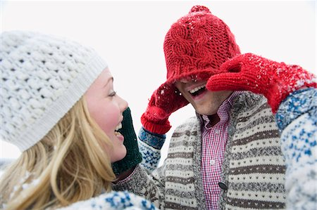 A young couple wearing woolen hats playing in the snow Stock Photo - Premium Royalty-Free, Code: 618-03612581