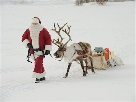 reindeer in snow - Santa Claus leading his reindeer and sleigh through the snow Stock Photo - Premium Royalty-Free, Code: 618-03612594