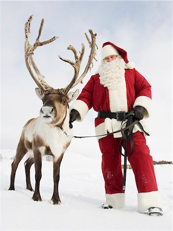reindeer in snow - Santa Claus standing with his reindeer Stock Photo - Premium Royalty-Free, Code: 618-03612597