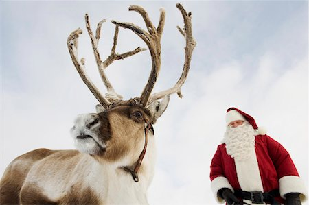 reindeer in snow - Santa Claus standing with his reindeer Stock Photo - Premium Royalty-Free, Code: 618-03612599