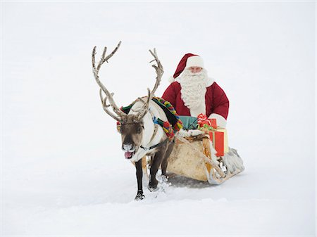 reindeer in snow - A reindeer pulling Santa Claus and his sleigh of presents Stock Photo - Premium Royalty-Free, Code: 618-03612592