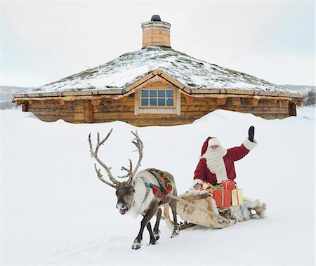reindeer in snow - A reindeer pulling Santa Claus and his sleigh, Santa Claus waving Stock Photo - Premium Royalty-Free, Code: 618-03612593