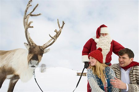 reindeer in snow - A young couple with Santa and his reindeer in the snow Stock Photo - Premium Royalty-Free, Code: 618-03612604