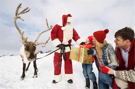 reindeer in snow - A young boy and his parents receiving a large present from Santa Claus Stock Photo - Premium Royalty-Free, Code: 618-03612605