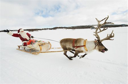 reindeer in snow - A reindeer pulling Santa Claus and his sleigh of presents through the snow Stock Photo - Premium Royalty-Free, Code: 618-03612606
