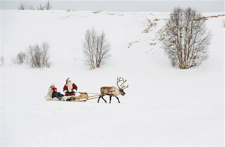 reindeer in snow - A mother and child having a sleigh ride with Santa Claus and his reindeer Stock Photo - Premium Royalty-Free, Code: 618-03612608