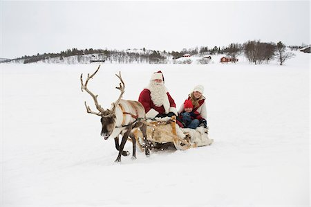 reindeer in snow - A mother and child having a sleigh ride with Santa Claus and his reindeer Stock Photo - Premium Royalty-Free, Code: 618-03612609