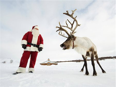 reindeer in snow - Santa Claus standing with his reindeer Stock Photo - Premium Royalty-Free, Code: 618-03612601
