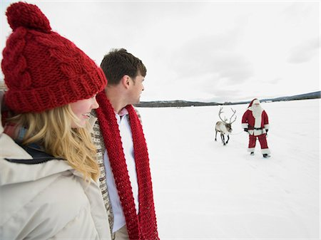 reindeer in snow - A young couple watching Santa Claus lead his reindeer through the snow Stock Photo - Premium Royalty-Free, Code: 618-03612602