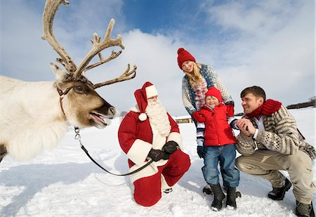reindeer in snow - A young boy and his parents meeting Santa Claus and his reindeer Stock Photo - Premium Royalty-Free, Code: 618-03612603