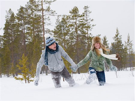 A young couple walking hand in hand through deep snow Stock Photo - Premium Royalty-Free, Code: 618-03612654