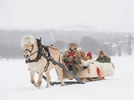 A horse pulling a sleigh full of people through the snow Stock Photo - Premium Royalty-Free, Code: 618-03612657