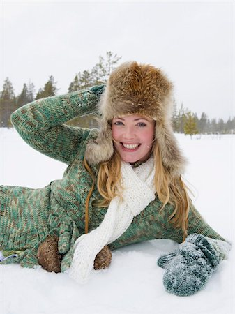 A young woman wearing a fur hat laying in the snow Stock Photo - Premium Royalty-Free, Code: 618-03612651