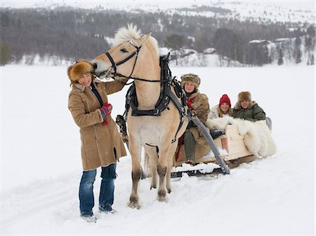 A horse pulling a sleigh full of people through the snow Stock Photo - Premium Royalty-Free, Code: 618-03612660