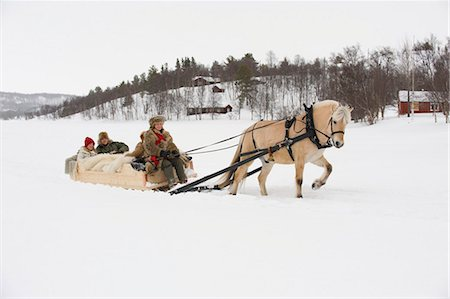 A horse pulling a sleigh full of people through the snow Stock Photo - Premium Royalty-Free, Code: 618-03612662