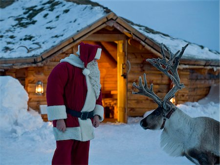 reindeer in snow - Santa Claus talking to his reindeer Stock Photo - Premium Royalty-Free, Code: 618-03612688