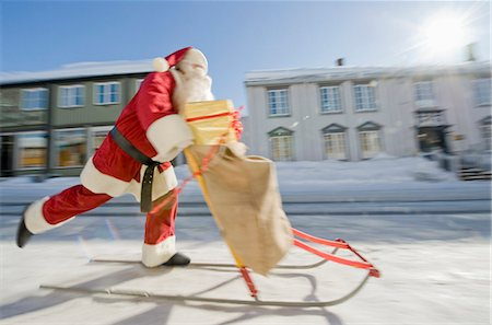 small town snow - Santa Claus on a sled with a sack full of presents Stock Photo - Premium Royalty-Free, Code: 618-03612718