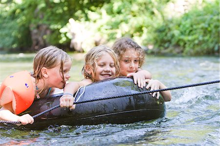 Three young girls floating down a river on an inflatable ring Stock Photo - Premium Royalty-Free, Code: 618-03612884