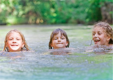 Three young girls swimming together in a river Stock Photo - Premium Royalty-Free, Code: 618-03612886