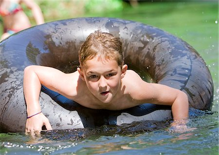 A young boy paddling in an inflatable ring Stock Photo - Premium Royalty-Free, Code: 618-03612887