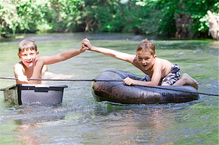 Two boys floating down a river holding hands Stock Photo - Premium Royalty-Free, Code: 618-03612888