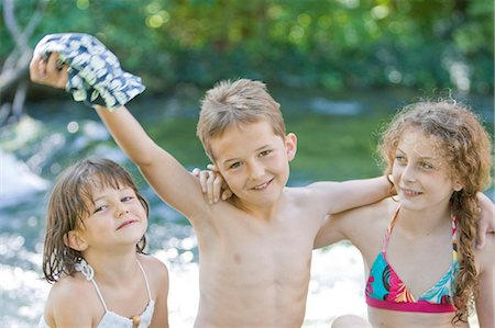 Three children in swimwear standing next to a river Stock Photo - Premium Royalty-Free, Code: 618-03612889