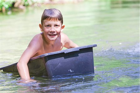 A young boy floating down a river in a plastic box Stock Photo - Premium Royalty-Free, Code: 618-03612881